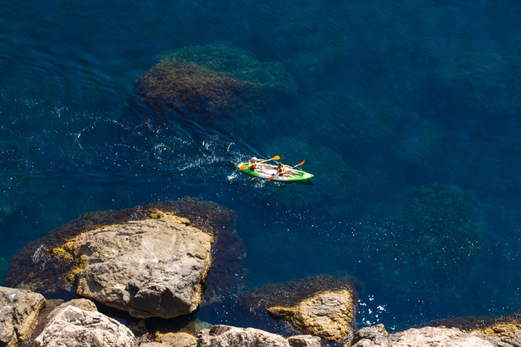 Top view of a kayak boats in shallow blue water of the Black Sea, Crimea