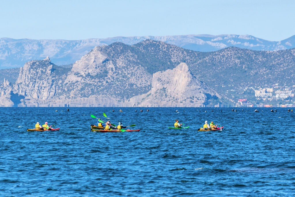 Sudak, Crimea - September 9, 2020: Tourists sail in kayaks on the Black Sea against the backdrop of mountains and the village of Novy Svet. Soft focus