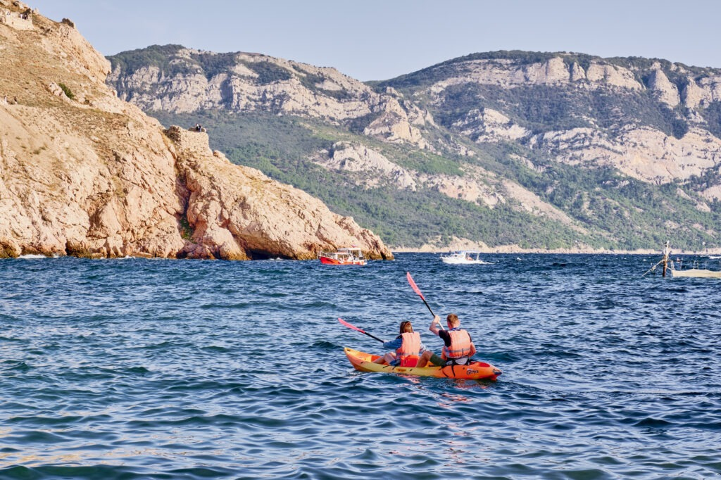 Sevastopol, Russia - October 6, 2020: A couple in a plastic kayak swims in the Balaklava bay against the background of the cape Aya, Crimea
